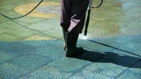 Очищая улицы города со шлангом воды Асфальт дворника очищая Сила работника моет обочину около тротуара внутри сток-видео