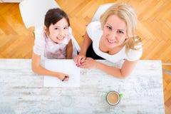 дочь помогая ее мати домашней работы Стоковые Изображения RF