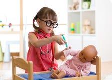 Оягнитесь девушка играя доктора с куклой в детском саде Стоковая Фотография RF