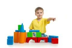Оягнитесь играть с цветастыми строительными блоками и указывая направлением Стоковое фото RF