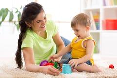Оягнитесь игра мальчика и матери вместе с игрушками чашки Стоковое Изображение RF