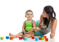 Оягнитесь игра мальчика и матери вместе с игрушкой конструкции установленной Стоковое Изображение