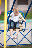 Оягнитесь катание девушки малыша на качании в спортивной площадке Стоковые Фото