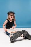 Оягнитесь книга чтения девушки с выражением лица пока сидящ на поле Стоковое фото RF