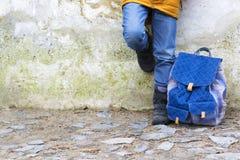 Оягнитесь ноги и рюкзак мальчика против стены Стоковое Фото