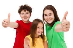 Малыши показывая ОДОБРЕННЫЙ знак изолированный на белой предпосылке Стоковая Фотография RF