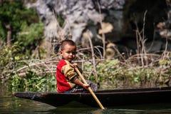 Оягнитесь помогать его папе полоща его традиционную пирогу вне sadan пещеры, Hpa-an, района Hpa-an, Мьянмы стоковое фото rf