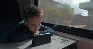 Оягнитесь при наушники наблюдая шарж на клетке в поезде сток-видео