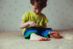 Оягнитесь при таблетка сидя на кровати и наблюдая шаржах Селективный фокус на ногах Милый мальчик в зеленой футболке и голубых бр Стоковое Изображение RF