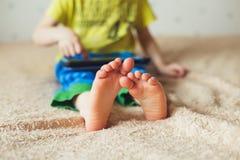 Оягнитесь при таблетка сидя на кровати и наблюдая шаржах Селективный фокус на ногах Милый мальчик в зеленой футболке и голубых бр Стоковые Фото