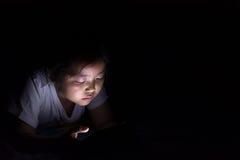 Оягнитесь при таблетка сидя на кровати и наблюдая шаржах на ноче Стоковое Изображение RF