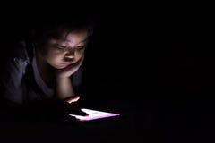 Оягнитесь при таблетка сидя на кровати и наблюдая шаржах на ноче Стоковые Фото