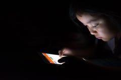 Оягнитесь при таблетка сидя на кровати и наблюдая шаржах на ноче Стоковые Изображения