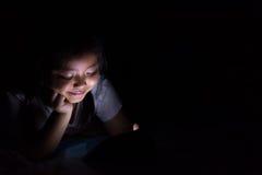 Оягнитесь при таблетка сидя на кровати и наблюдая шаржах на ноче Стоковые Изображения RF
