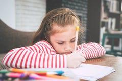 Оягнитесь расцветка карандаша девушки на бумаге в живущей комнате Стоковое Изображение