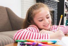 Оягнитесь расцветка карандаша девушки на бумаге в живущей комнате Стоковая Фотография RF