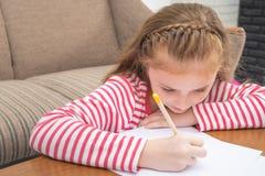 Оягнитесь расцветка карандаша девушки на бумаге в живущей комнате Стоковые Изображения