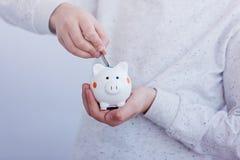 Оягнитесь рука кладя монетку в копилку или денежный ящик Стоковое фото RF