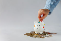 Оягнитесь рука кладя монетку в копилку или денежный ящик Стоковые Изображения RF