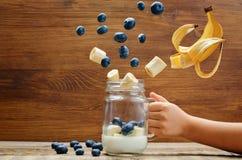 Оягнитесь рука ` s с smoothie банана голубики с кусками летания Стоковая Фотография RF