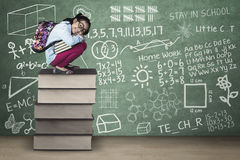 Оягнитесь сидение на корточках на книгах с doodles в классе Стоковое Изображение RF