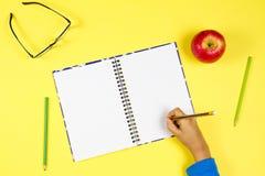 Оягнитесь сочинительство руки на тетради, красочных карандашах, стеклах и свежем яблоке на желтой предпосылке стоковые фотографии rf