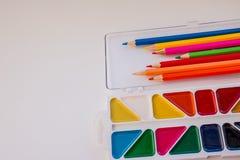 Оягнитесь стол ` s с красочными карандашами, щетки и акварели, взгляд сверху с космосом экземпляра задняя школа к рисуя поставкы стоковое изображение