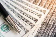 100 долларовые банкноты и ручек на деревянном Стоковое фото RF