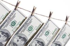 100 долларовых банкнот вися от веревки для белья на белизне Стоковое Фото