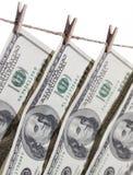 100 долларовых банкнот вися от веревки для белья на белизне Стоковое фото RF