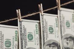 100 долларовых банкнот вися от веревки для белья на темной предпосылке Стоковая Фотография