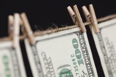 100 долларовых банкнот вися от веревки для белья на темной предпосылке Стоковая Фотография RF