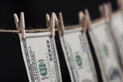 100 долларовых банкнот вися от веревки для белья на темной предпосылке Стоковые Фотографии RF