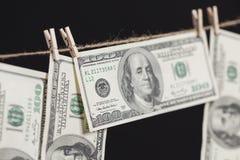 100 долларовых банкнот вися от веревки для белья на темной предпосылке Стоковые Фото