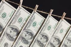 100 долларовых банкнот вися от веревки для белья на темной предпосылке Стоковые Изображения