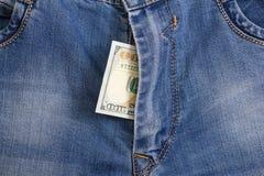 100 долларовых банкнот внутри голубых джинсов гульфика Стоковые Фото