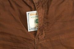 100 долларовых банкнот внутри джинсов коричневого цвета гульфика Стоковые Изображения RF
