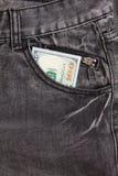 100 долларовых банкнот внутри передних карманных джинсов Стоковое фото RF