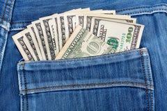 100 долларовых банкнот вставляя в заднем карманн джинсов джинсовой ткани Стоковые Фотографии RF