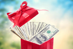 100 долларовых банкнот в большой красной присутствующей коробке Стоковая Фотография