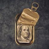 100 долларовых банкнот в открытой пустой жестяной коробке рыб сардины Стоковое фото RF