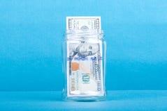 100 долларовых банкнот в стеклянном опарнике, взгляд со стороны, голубая предпосылка Стоковые Фотографии RF
