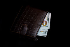 100 долларовых банкнот в темном кожаном изолированном портмоне Стоковые Изображения