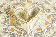 100 долларовых банкнот в форме сердца Стоковое фото RF
