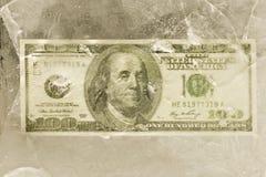 100 долларовых банкнот за треснутым льдом Стоковые Фотографии RF