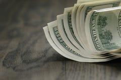 100 долларовых банкнот на деревянной таблице Стоковые Изображения RF