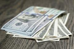 100 долларовых банкнот на деревянном столе Стоковые Фото