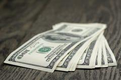 100 долларовых банкнот на деревянном столе Стоковые Изображения RF