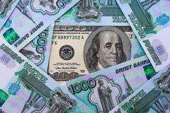 100 долларовых банкнот на предпосылке русских рублевок Стоковые Фотографии RF