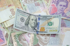 100 долларовых банкнот на предпосылке украинского hryvnia Стоковая Фотография